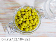 Home canning of summer bean crop, vegetable vegetarian diet healthy food, natural green peas marinated in a glass jar top view on table background. Стоковое фото, фотограф Светлана Евграфова / Фотобанк Лори