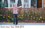 Купить «A man in white hat dancing russian folk dance by the fence with flowers», видеоролик № 32184851, снято 21 февраля 2020 г. (c) Константин Шишкин / Фотобанк Лори