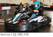 Купить «Female racer in helmet driving kart on track», фото № 32185115, снято 18 марта 2019 г. (c) Яков Филимонов / Фотобанк Лори