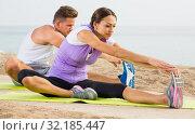 Positive couple practising yoga poses on sunny beach. Стоковое фото, фотограф Яков Филимонов / Фотобанк Лори