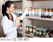 Купить «Female customer examining various canned beans», фото № 32185483, снято 23 ноября 2016 г. (c) Яков Филимонов / Фотобанк Лори