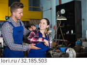 Купить «Man who is training female to repairing drill», фото № 32185503, снято 10 октября 2017 г. (c) Яков Филимонов / Фотобанк Лори