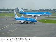 Самолеты Boeing 737-8К2 и Boeing 747-400М авиакомпании KLM Royal Dutch Аирлинес на летном поле аэропорта Схипхол пасмурным утром. Амстердам, Нидерланды (2017 год). Редакционное фото, фотограф Виктор Карасев / Фотобанк Лори