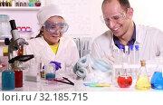Купить «A young chemistry teacher conducts a chemical experiment with foam  in primary school», видеоролик № 32185715, снято 17 сентября 2019 г. (c) Алексей Кузнецов / Фотобанк Лори
