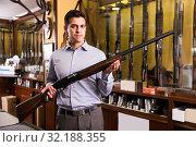 Man owner of hunting store standing with shotgun. Стоковое фото, фотограф Яков Филимонов / Фотобанк Лори
