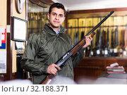 Купить «Confident hunter male wearing windbreaker in hunting shop with rifle in hands», фото № 32188371, снято 11 декабря 2017 г. (c) Яков Филимонов / Фотобанк Лори