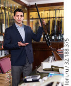 Handsome adult male in hunting shop with rifle in hands. Стоковое фото, фотограф Яков Филимонов / Фотобанк Лори