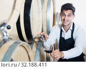 Купить «Seller pouring wine in cellar», фото № 32188411, снято 22 сентября 2019 г. (c) Яков Филимонов / Фотобанк Лори