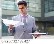 Купить «Concentrated businessman reading documents», фото № 32188427, снято 8 мая 2017 г. (c) Яков Филимонов / Фотобанк Лори