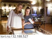 Купить «Girl with woman looking with interest at art objects under glass in museum», фото № 32188527, снято 21 октября 2018 г. (c) Яков Филимонов / Фотобанк Лори