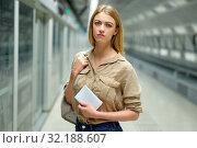 Купить «Young woman waiting for train at subway station; looking at paper», фото № 32188607, снято 31 марта 2019 г. (c) Яков Филимонов / Фотобанк Лори