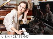 Купить «Beautiful girl chooses a piano in a music store», фото № 32188643, снято 16 апреля 2019 г. (c) Яков Филимонов / Фотобанк Лори