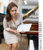Купить «Saleswoman assistant in piano music store», фото № 32188651, снято 16 апреля 2019 г. (c) Яков Филимонов / Фотобанк Лори
