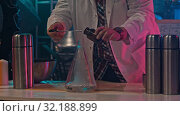 Купить «Scientist puts the substance into a flask to perform an experiment and stirs it up», видеоролик № 32188899, снято 25 февраля 2020 г. (c) Константин Шишкин / Фотобанк Лори