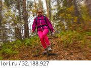 Купить «Woman traveler descends from a hill in the autumn forest, radial blur background», фото № 32188927, снято 15 сентября 2019 г. (c) Евгений Харитонов / Фотобанк Лори