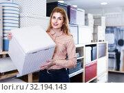 Купить «Glad saleswoman offering soft pouf in store», фото № 32194143, снято 15 января 2018 г. (c) Яков Филимонов / Фотобанк Лори