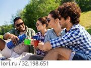 Купить «happy friends drinking tea from thermos in summer», фото № 32198651, снято 15 июня 2019 г. (c) Syda Productions / Фотобанк Лори