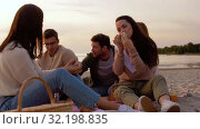 Купить «happy friends eating sandwiches at picnic on beach», видеоролик № 32198835, снято 9 сентября 2019 г. (c) Syda Productions / Фотобанк Лори
