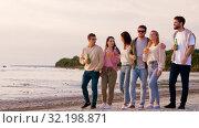 friends with non alcoholic drinks walking on beach. Стоковое видео, видеограф Syda Productions / Фотобанк Лори