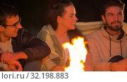 Купить «group of friends sitting at camp fire at night», видеоролик № 32198883, снято 9 сентября 2019 г. (c) Syda Productions / Фотобанк Лори