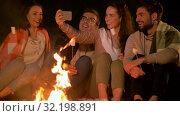 Купить «friends taking selfie at night camp fire», видеоролик № 32198891, снято 9 сентября 2019 г. (c) Syda Productions / Фотобанк Лори
