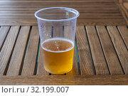 Купить «Beer with white foam in a plastic transparent cup on a wooden table», фото № 32199007, снято 2 сентября 2019 г. (c) Валерий Смирнов / Фотобанк Лори