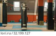 Купить «A man bodybuilder pulls up the punching bag from the ground», видеоролик № 32199127, снято 21 сентября 2019 г. (c) Константин Шишкин / Фотобанк Лори