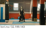 Купить «A man bodybuilder puts up the punching bag from the ground and putting it on his shoulder», видеоролик № 32199143, снято 21 сентября 2019 г. (c) Константин Шишкин / Фотобанк Лори