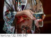 Купить «Женщина в кимоно предлагает гостям чашку свежеприготовленного чая во время традиционной японской чайной церемонии», фото № 32199147, снято 31 августа 2019 г. (c) Николай Винокуров / Фотобанк Лори