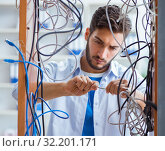 Electrician trying to untangle wires in repair concept. Стоковое фото, фотограф Elnur / Фотобанк Лори