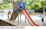 Купить «Cheerful boy and girl play games and running around sliding toy in park», видеоролик № 32205551, снято 23 июля 2018 г. (c) Яков Филимонов / Фотобанк Лори