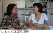 Купить «Two smiling women sitting at home table with laptop», видеоролик № 32205599, снято 27 мая 2019 г. (c) Яков Филимонов / Фотобанк Лори
