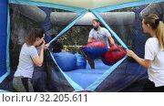 Купить «Expressive bearded guy in big boxing gloves having fun on inflatable ring in outdoor amusement park», видеоролик № 32205611, снято 29 мая 2019 г. (c) Яков Филимонов / Фотобанк Лори