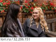 Купить «Two girlfriends are talking to each other», фото № 32206151, снято 19 сентября 2019 г. (c) Евгений Харитонов / Фотобанк Лори