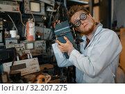 Купить «Scientist in glasses holds electrical device», фото № 32207275, снято 17 июня 2019 г. (c) Tryapitsyn Sergiy / Фотобанк Лори