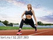 Купить «Female jogger in sportswear, training on stadium», фото № 32207383, снято 2 июля 2019 г. (c) Tryapitsyn Sergiy / Фотобанк Лори