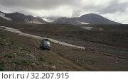 Купить «Japanese SUV Mitsubishi Delica driving on mountain road in direction of active volcano», видеоролик № 32207915, снято 16 августа 2019 г. (c) А. А. Пирагис / Фотобанк Лори