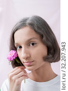 Купить «Portrait of a brown-Eyed girl on a pink background, holding a flower of lilac chrysanthemum», фото № 32207943, снято 31 августа 2019 г. (c) Катерина Белякина / Фотобанк Лори