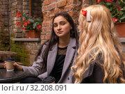 Купить «Girl in disbelief  listens to her friend on a bench with coffee outdoors», фото № 32208091, снято 19 сентября 2019 г. (c) Евгений Харитонов / Фотобанк Лори