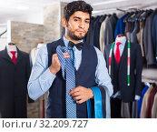 Customer man is picking up tie for waistcoat. Стоковое фото, фотограф Яков Филимонов / Фотобанк Лори