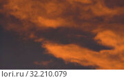 Купить «Yellow-orange clouds glowing at sunset floating across dramatic purple sky», видеоролик № 32210079, снято 10 сентября 2019 г. (c) А. А. Пирагис / Фотобанк Лори