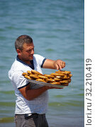 Мужчина продает бублики с кунжутом на пляже в Турции (2019 год). Редакционное фото, фотограф Natalya Sidorova / Фотобанк Лори
