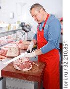 Купить «Smiling man seller cutting meat in shop», фото № 32210851, снято 22 июня 2018 г. (c) Яков Филимонов / Фотобанк Лори