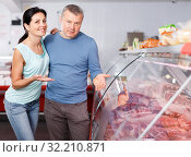 Купить «Positive couple customers choosing meat in shop», фото № 32210871, снято 22 июня 2018 г. (c) Яков Филимонов / Фотобанк Лори