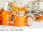 Cosmetology, traditional alternative medicine, herbal medicine, natural sea buckthorn vegetable oil in a glass jar on a table background, healthy juice, branches with a harvest of fresh ripe berries. Стоковое фото, фотограф Светлана Евграфова / Фотобанк Лори