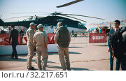 Купить «30 AUGUST 2019 MOSCOW, RUSSIA: an outdoors airplane exposition - workers removing the helicopter exhibit from the exposition area - another workers standing on the foreground and talking to each other», видеоролик № 32217651, снято 19 октября 2019 г. (c) Константин Шишкин / Фотобанк Лори