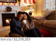 Купить «Couple at home at Christmas time», фото № 32218203, снято 6 сентября 2019 г. (c) Wavebreak Media / Фотобанк Лори