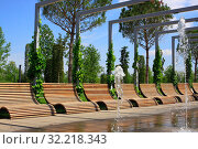 Купить «Лежачие скамейки для отдыха в парке Краснодар, Россия. Деревянные кресла для релакса. Городской летний пейзаж с видом на аллею с креслами и фонтаны», фото № 32218343, снято 2 августа 2019 г. (c) Дорощенко Элла / Фотобанк Лори