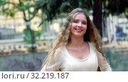 Купить «Happy young woman in autumn city park is laughing for joy», видеоролик № 32219187, снято 24 сентября 2019 г. (c) Gennadiy Poznyakov / Фотобанк Лори