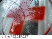 Купить «Крупным планом красный крест на стекле автомобиля Скорой помощи в городе Москве, Россия», фото № 32219227, снято 21 сентября 2019 г. (c) Николай Винокуров / Фотобанк Лори
